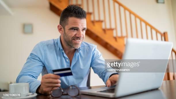 modernen geschäftsmann mit laptop und kreditkarte - bucht stock-fotos und bilder
