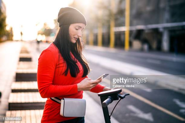 a modern busy woman using a mobile phone while getting ready to join the traffic on an electric scooter in the street downtown - waist pack stock pictures, royalty-free photos & images