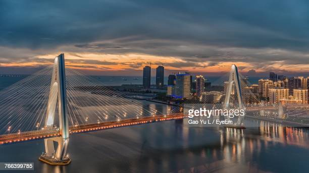 modern cable-stayed bridge over river in city during sunset - haikou stock pictures, royalty-free photos & images