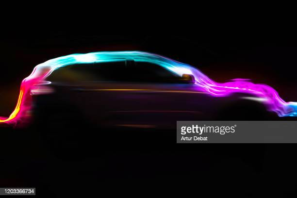 modern car with aerodynamic colorful light trail at night. - electric car stock pictures, royalty-free photos & images