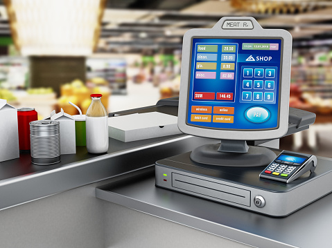 Modern cash register with POS machine standing next to belt with supermarket items 973111634
