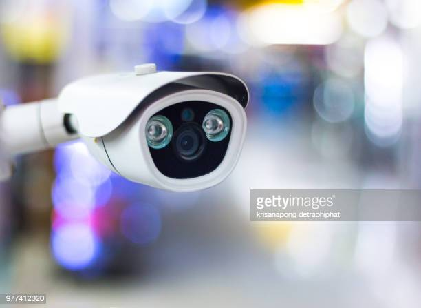 Modern CCTV camera on a wall.Concept of surveillance and monitoring. Toned image double exposure mock up