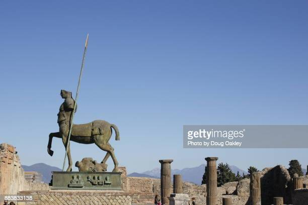 modern centaur sculpture towers over ruins of pompeii, italy - centaur stock photos and pictures