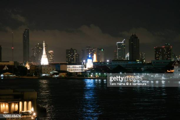 Modern city buildings and Chao Phraya River in Bangkok in the sunset