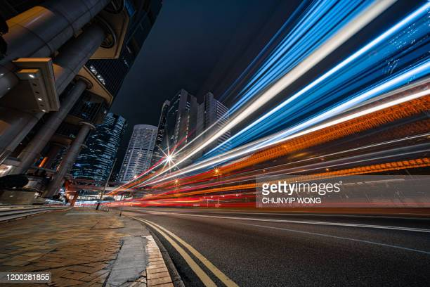 modern city traffic at night, hong kong - long exposure stock pictures, royalty-free photos & images