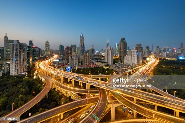 modern city with highway interchange in shanghai, china. - affollato foto e immagini stock