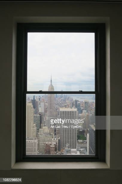 modern cityscape against sky seen through window - window frame stock pictures, royalty-free photos & images