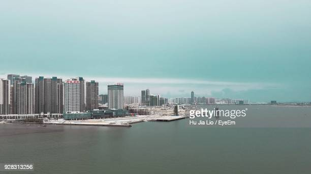 modern cityscape by sea against clear sky - zhanjiang stock photos and pictures