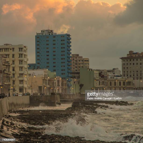 modern cityscape by sea against sky - carvajal stock photos and pictures