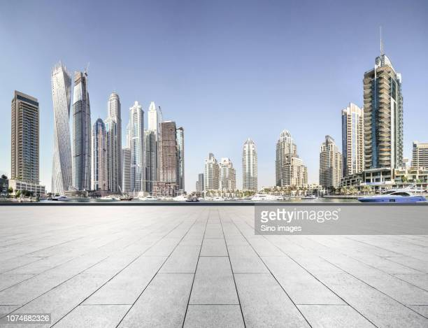 modern cityscape with skyscrapers seen from pavement, dubai - image stock pictures, royalty-free photos & images