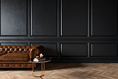 Modern classic black interior with capitone chester leather brown sofa, coffee table, wood floor, mouldings. 3d render interior mock up.