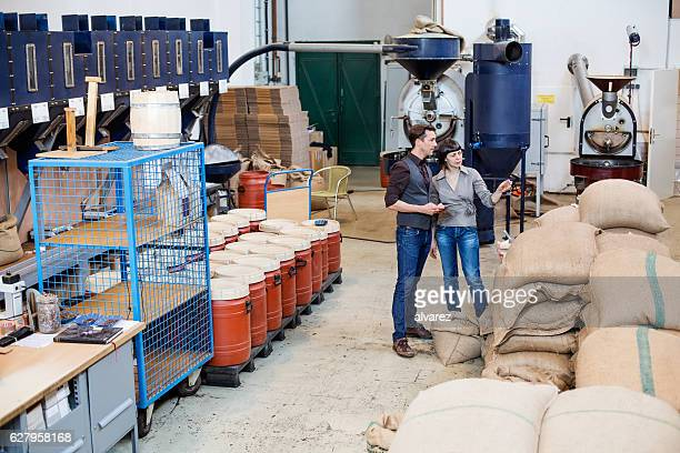 Modern coffee roaster factory with two people working
