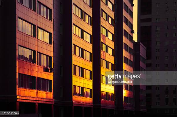 Modern color multi-stored building. Sunlight shining at glass wall