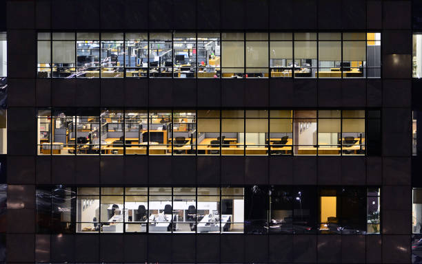 Modern commercial building in Sao Paulo, with empty workstations viewed through its windows