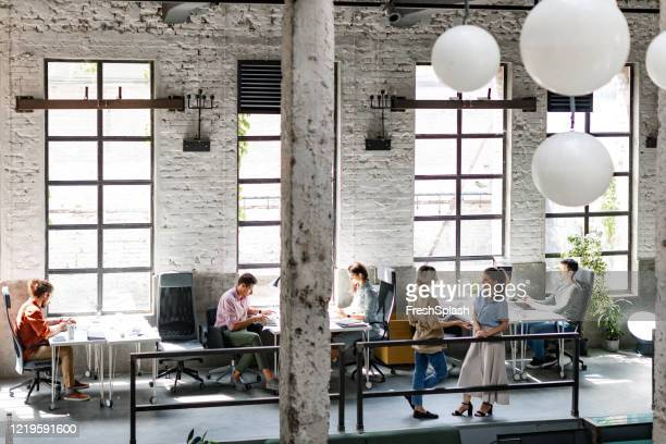 modern companies:  group of young business people at a spacious loft open space coworking office working together - wide angle stock pictures, royalty-free photos & images