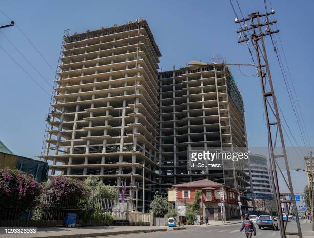 Modern construction project dwarfs an older building of classic Italian design commonly found in the section of Addis Ababa known as Piassa on...