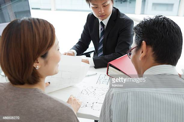 Modern couple listening to manager explanation about conditions of mortgage