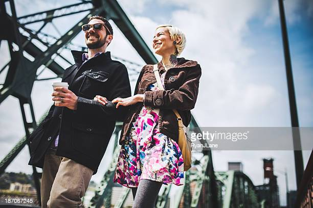 modern couple on portland's hawthorne bridge - portland oregon stock photos and pictures