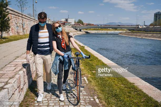 modern couple wearing surgical masks and gloves during their walk on a quayside - quayside stock pictures, royalty-free photos & images