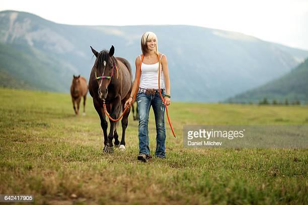 Modern cowgirl walking her horses.