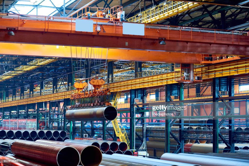 Modern crane moving steel pipe : Stock Photo