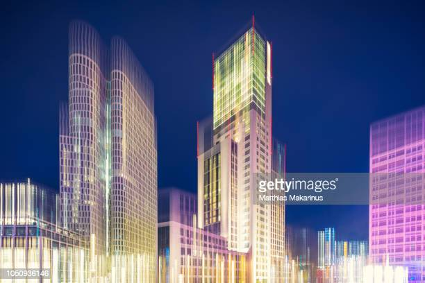 modern creative zoom business building district night szene in berlin with lights - makarinus stock photos and pictures