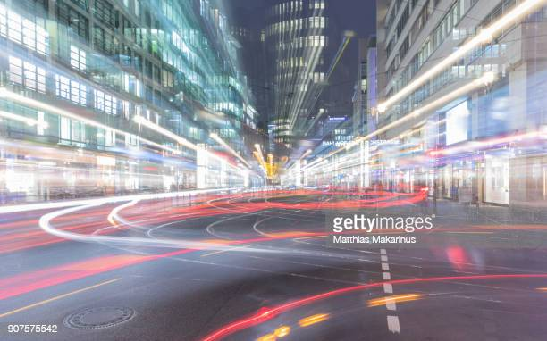 modern creative zoom rush hour night street szene in berlin with traffic lights - makarinus stock photos and pictures