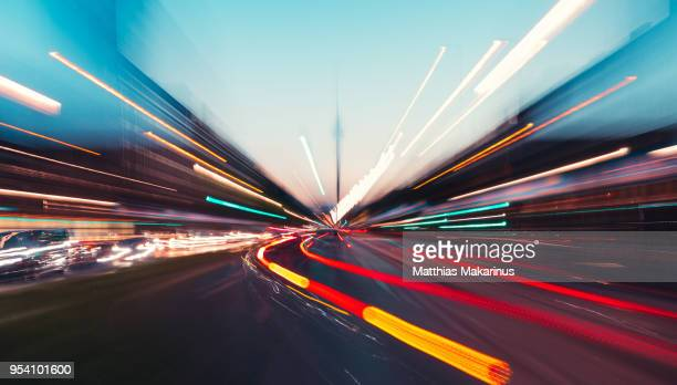 modern creative zoom rush hour night street szene in berlin with traffic lights - verkehrswesen stock-fotos und bilder