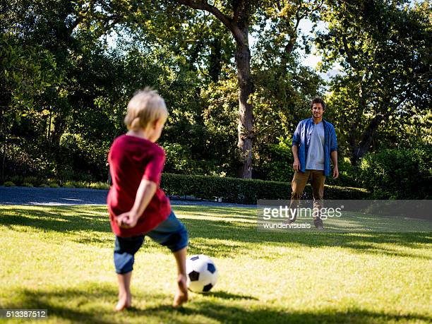 Modern Dad and Little Boy Playing Ball, Barefoot, in Garden