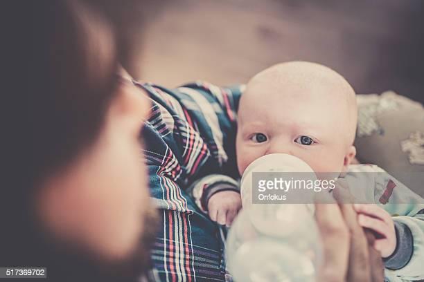 Moderne Vater sein Baby füttern Junge mit Flasche