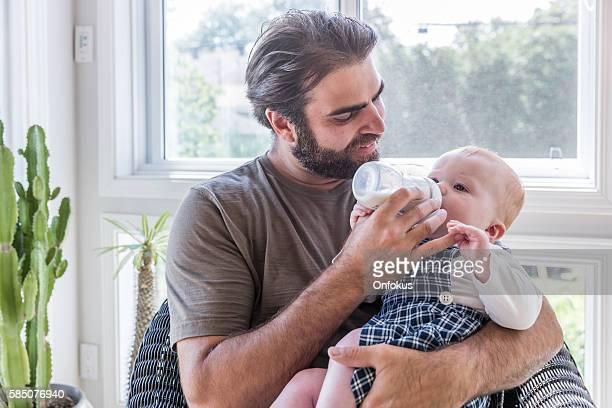 Modern Dad Feeding his Baby Boy with Milk Bottle