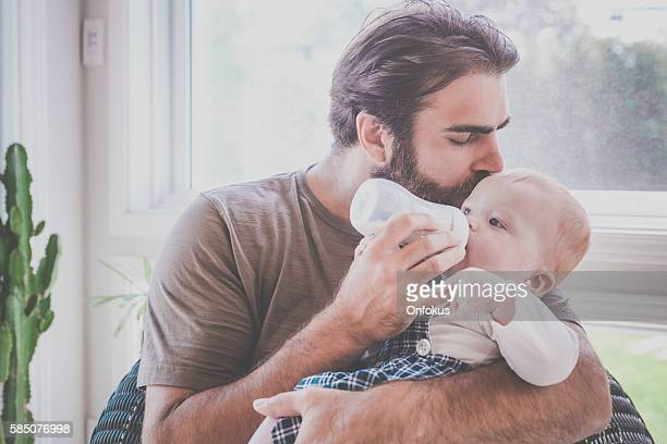 Modern Dad Feeding his Baby Boy with Milk Bottle