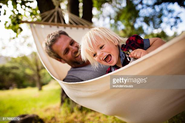 Modern dad hugs his blond child on hammock in garden