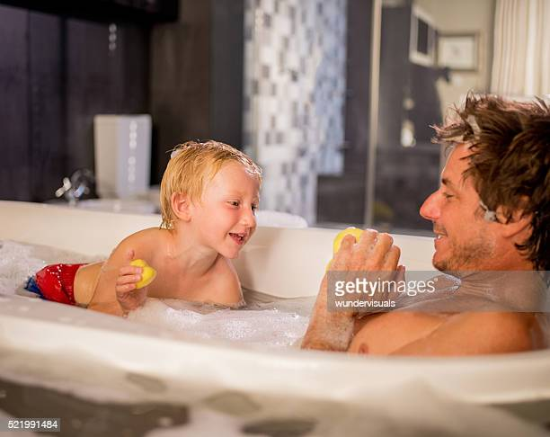 Modern Dad Plays with Son in Bubble Bath at Home
