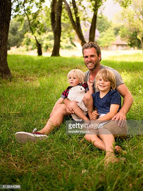 Modern dad sitting at park with his two children