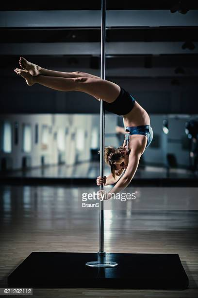 modern dancer dancing on a pole in a studio. - pole dance photos et images de collection