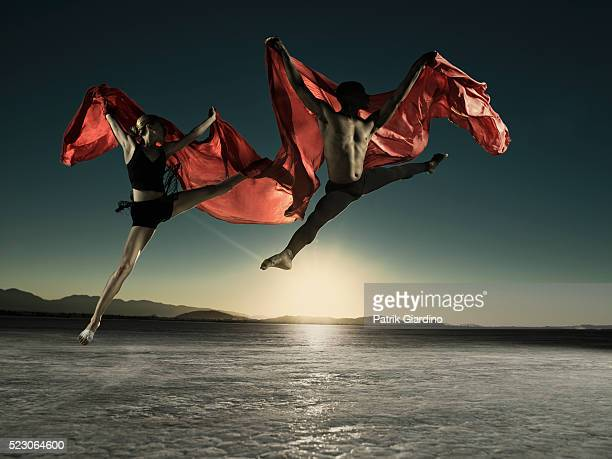 modern dancers with scarves jumping - performing arts event stock pictures, royalty-free photos & images