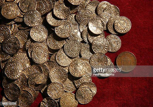 A modern day one pence coin is displayed with Anglo Saxon silver pennies at The British Museum on February 10 2015 in London England Rare coins and...