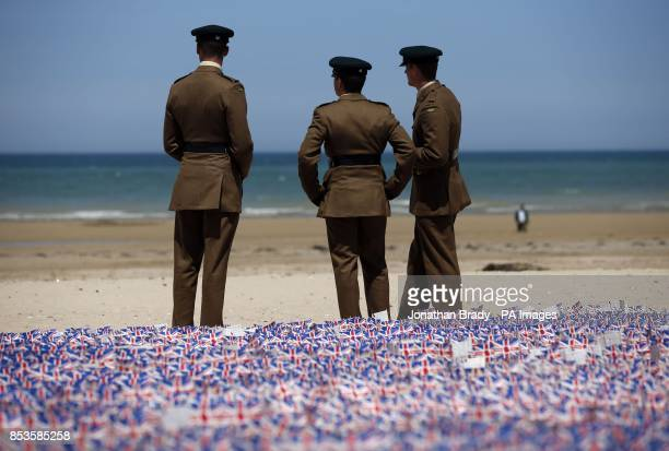 Modern day soldiers stand by union flags planted by the British Legion at Gold Beach Asnelles Normandy France as part of the celebrations to mark the...