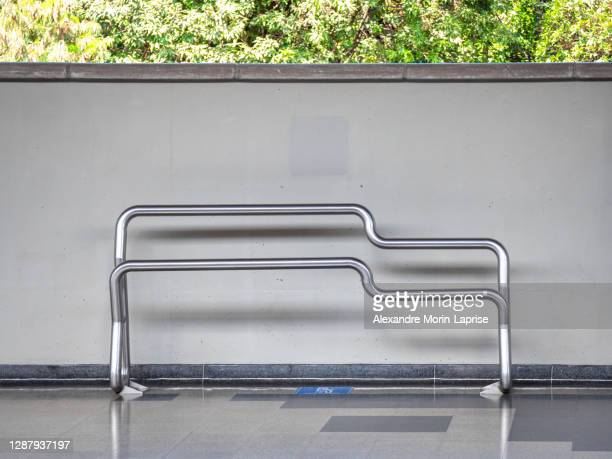 modern design stainless metal pipes bench in subway station by a white wall - chairperson stock pictures, royalty-free photos & images