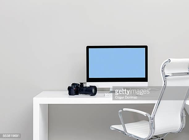 Modern desk with computer and digital camera
