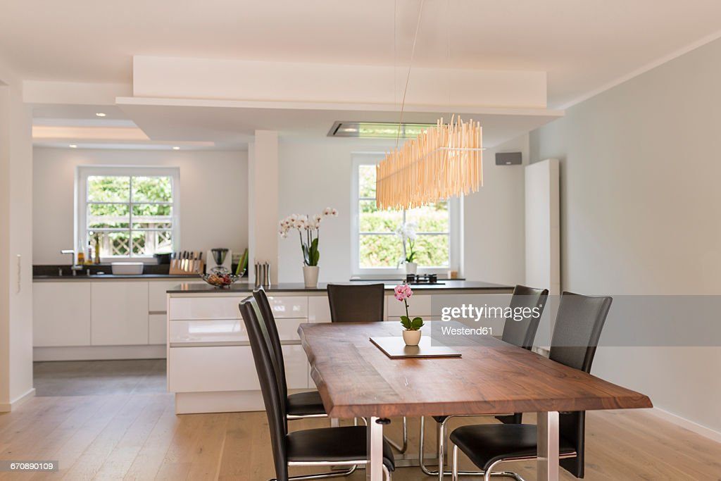 Modern dining area with open plan kitchen in the background : Stock Photo