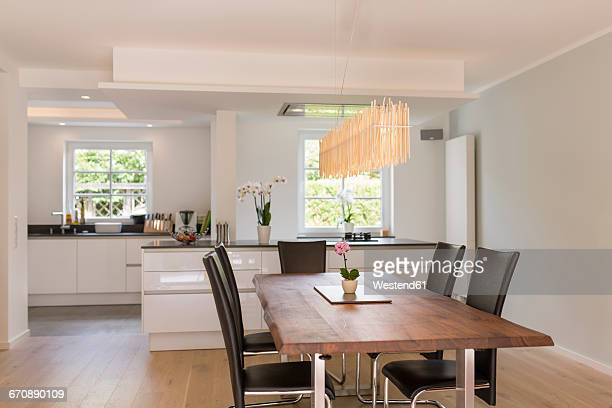 modern dining area with open plan kitchen in the background - dining room stock pictures, royalty-free photos & images