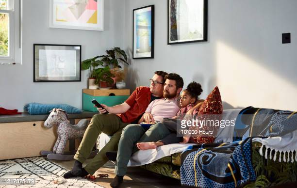 modern diverse family eating popcorn together on sofa - multi ethnic group stock pictures, royalty-free photos & images
