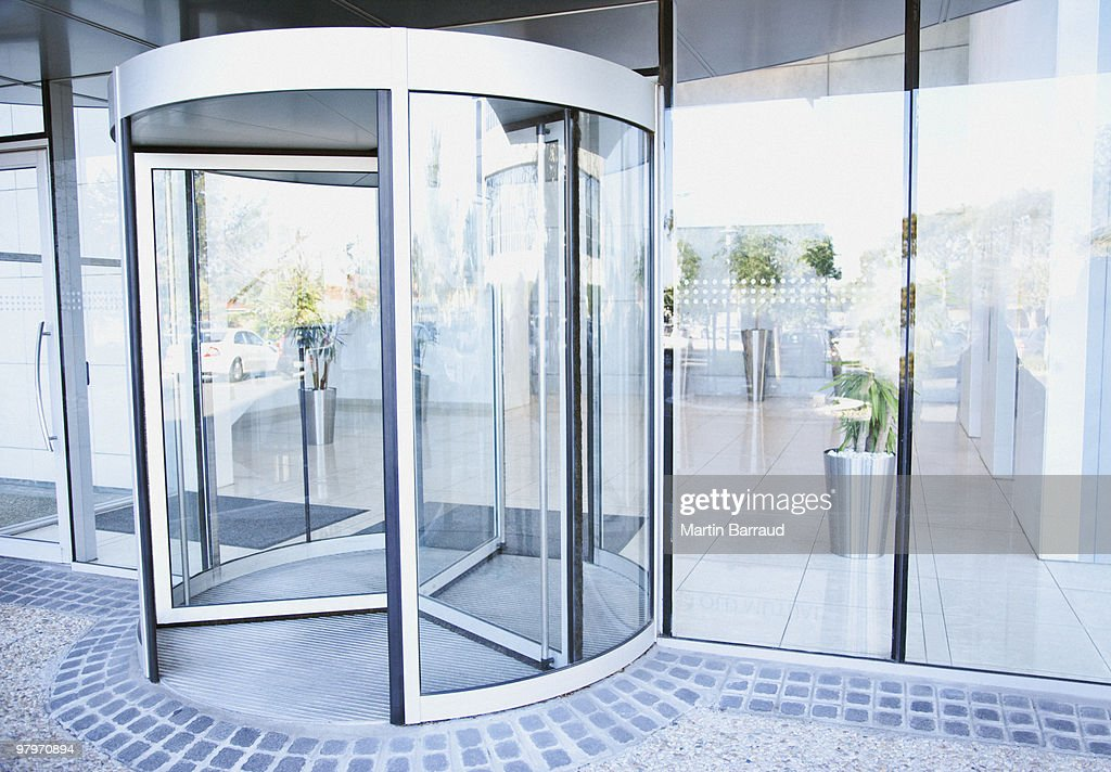 Modern entrance with revolving door : Stock Photo
