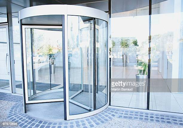 modern entrance with revolving door - entrance stock pictures, royalty-free photos & images