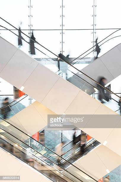 modern escalator with blurred people - vertikal stock-fotos und bilder