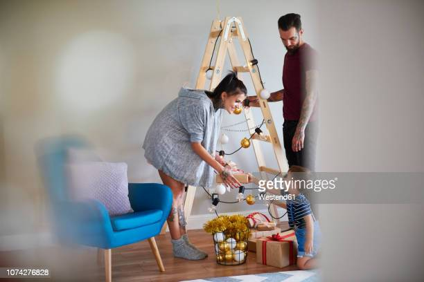 modern family at home at christmas time using ladder as christmas tree - family at home stock photos and pictures