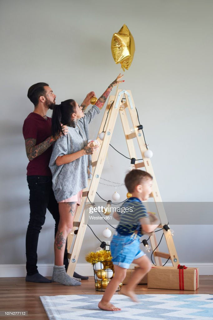 Modern Family Decorating The Home At Christmas Time Using Ladder As Christmas Tree High Res Stock Photo Getty Images