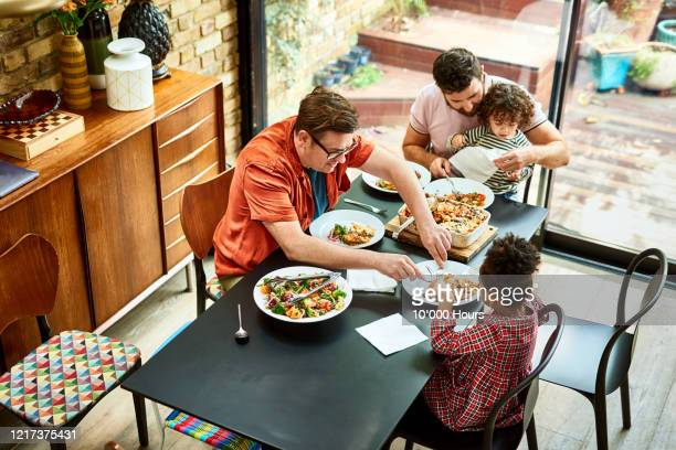modern family enjoying vegetarian food together during lockdown - vegetarian food stock pictures, royalty-free photos & images